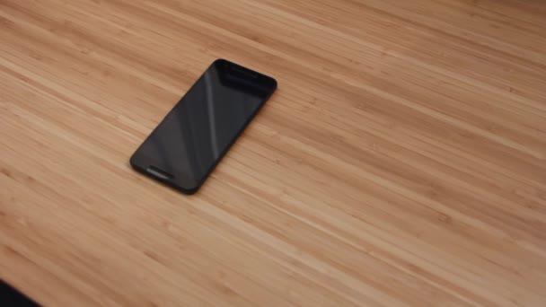 Techniker oder Ingenieur demontieren defekte Komponenten Smartphone zur Reparatur oder ersetzen neue Smartphone-Akku auf Bambus-Schreibtisch