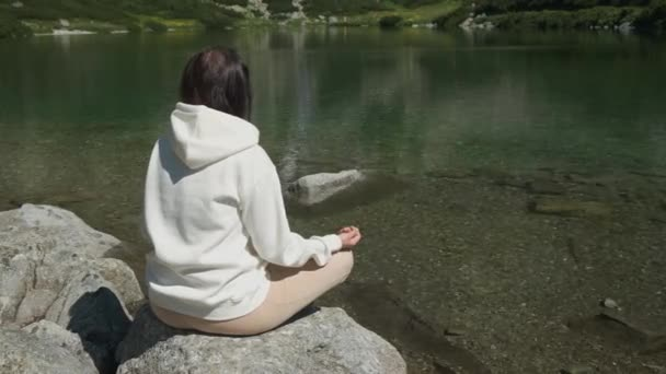 Turn around young woman in a white hoodie practicing yoga on a lake shore with transparent water with an amazing view on waterfall with copy space. Meditation and recreation in nature between