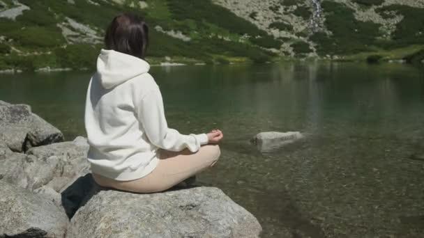 Otočte se mladá žena v bílé mikině cvičit jógu na břehu jezera s průhlednou vodou s úžasným výhledem na vodopád s kopírovacím prostorem. Meditace a rekreace v přírodě mezi