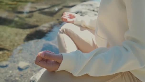 Zblízka žena cvičit jógu v lotosovém postoji na břehu jezera.