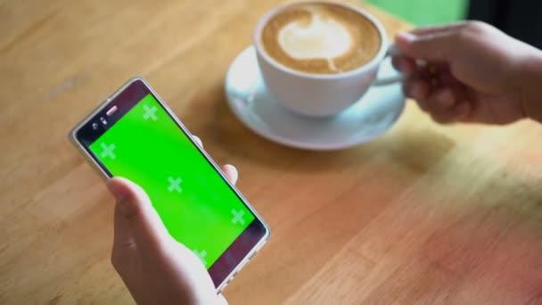 Fabion chroma klíč na smartphone. Ženy pracují nebo pomocí smartphone v kavárně, jednou rukou drží bílé café pozdní pohár a pití a další drží mobilní telefon, 4 k video