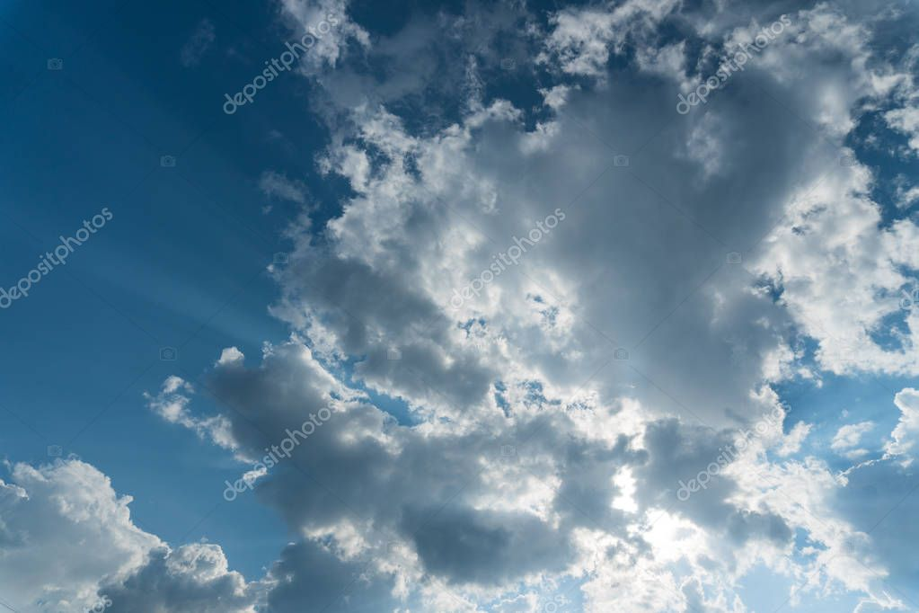 Clouds with sun rays on the blue sky