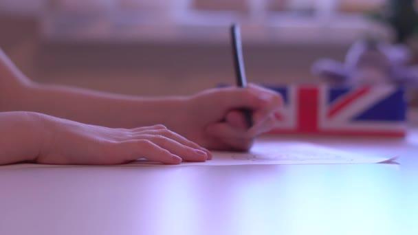 Detailní záběr na dívčí ruce na list papíru obrázek, Pencil Box s vlajkou Velké Británie na bílém stole s rozmazané pozadí