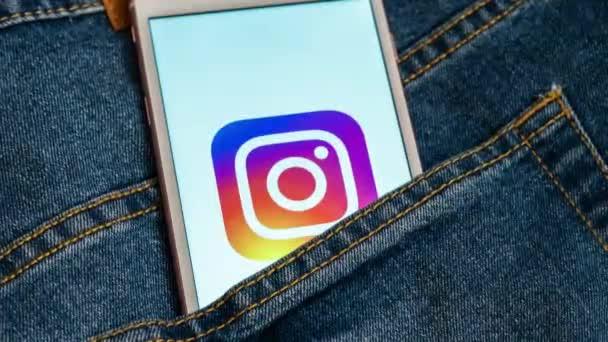 Tallinn/Estonsko-19. května 2019: bílý telefon s logem sociálních médií Instagram na obrazovce. Ikona sociálního média. Na pozadí džínsů. Ilustrace mediálního média nebo koncepce marketingu.
