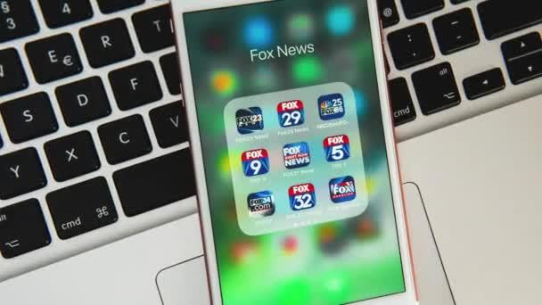 Palo Alto/USA-Srpen 08: bílý Apple iPhone s ikonami různých mediálních aplikací Fox News na obrazovce. Ikony mediálních médií pro ilustraci konceptu novinek nebo marketingu