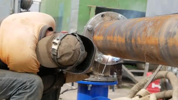 Svařování potrubí. Pracovník svářeč svařování potrubí pomocí elektrod. Elektrody pro svařování a jiskry.
