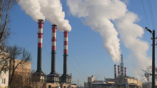 Znečištění ovzduší z průmyslových závodů. Průmyslové dýmky. Červená s bílým potrubí