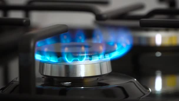Close side view natural blue gas ignites and burns in cooker burner against new black gas stove (cooktop)