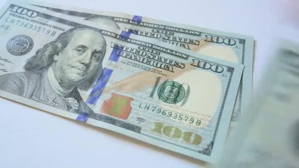 Hundred dollar bills on a table.