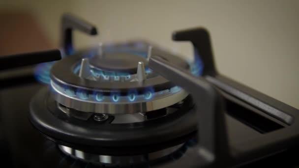 Seitenansicht Erdgas entzündet sich und verbrennt im Herdbrenner gegen neuen schwarzen Gasherd (Kochfeld))