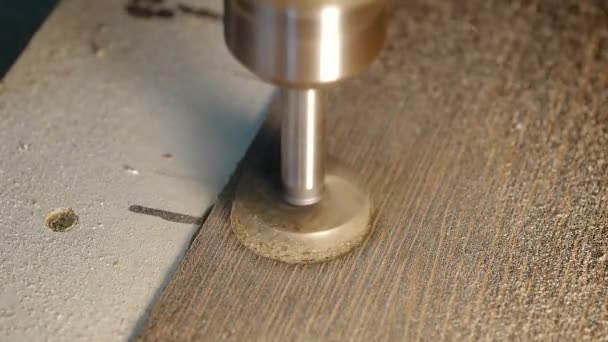 Close-up a drill press with a drill bit mounted in the chuck to drill a hole into a piece of wood particle board.