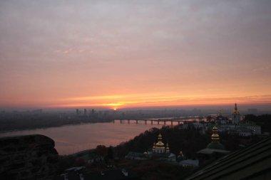 Kiev Pechersk Lavra on hill of Dnieper river at sunset
