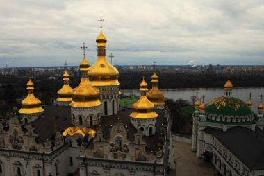 Kiev Pechersk Lavra with golden domes on hill of Dnieper river on background