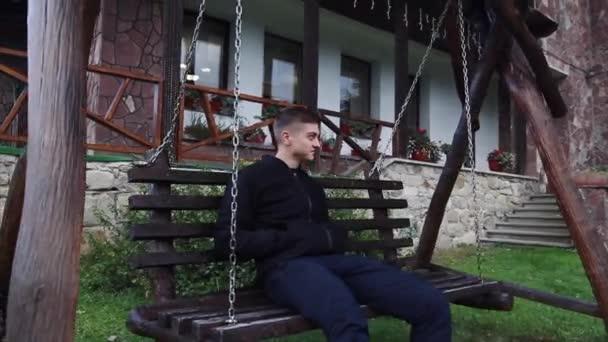 Mladý muž sedí na houpačce poblíž verandě domu a se dívá na les v mlze
