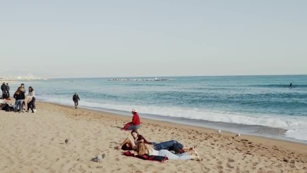 Lidé relaxovat na pláži Barcelona v zimě a pozorovat bouřlivé moře