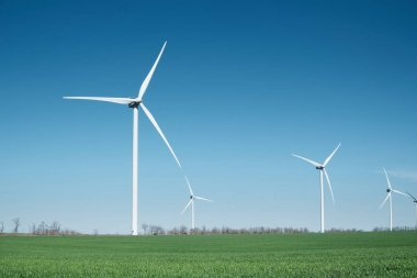 Wind power station on field. Technology and inovation. Green energy composition. Wind turbines. Industrial landscape