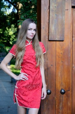 Female model from Poland wearing traditional Chinese dress in red color. Woman standing at park gate.