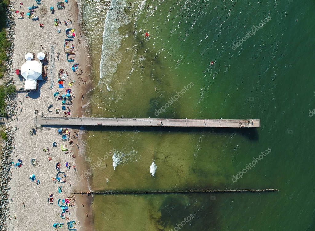 Aerial view on wooden pier on sea with sand beach and breakwaters.