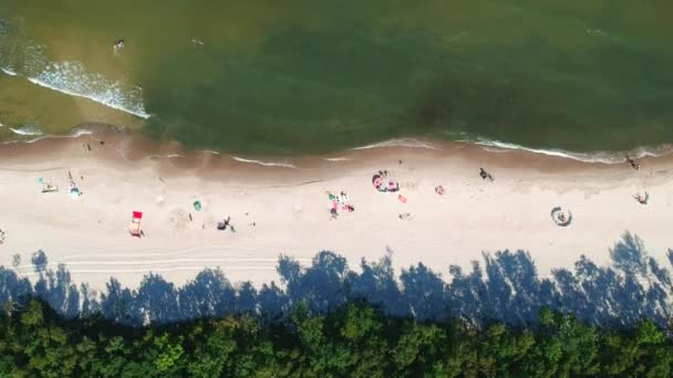 Aerial view on sand beach with sunbathers and sea waves