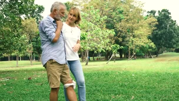 Žena se postarat starší muž s bolestí kolena v parku