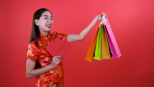 Woman in qipao chinese dress holding money in red chinese pocket and shopping bag isolated on red background