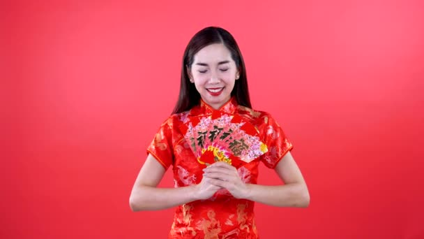 Woman in qipao chinese dress holding money isolated on red background