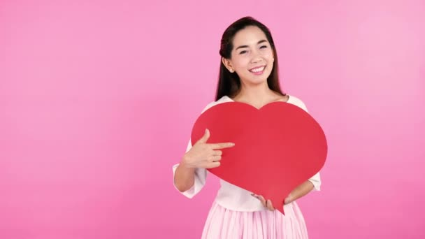 Woman holding red heart shape isolated on pink background