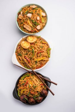 Manchurian Hakka / Schezwan noodles with chicken and egg, popular indochinese food served in a bowl. selective focus