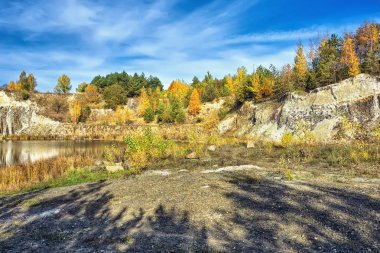 Autumn landscape - rocky shore of the lake, where trees with yellowed leaves.