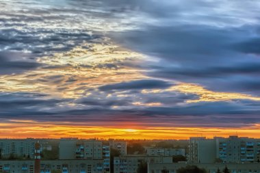Sky with clouds over city at sunset.