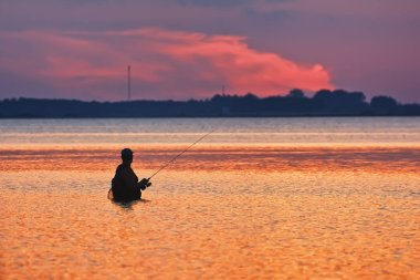 Fisherman silhouette against the backdrop of the sunset over the lake.