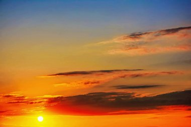 Sun at sunrise sunset with clouds on a blue sky.