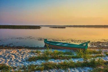 Sunrise on the lake, fishing boat on the shore.