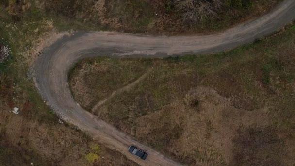 Letecký pohled shora automobilu na malé silnici s ostrými zatáčkami. Letecký pohled na staré černé bmw na venkovské silnici s ostrými zatáčkami