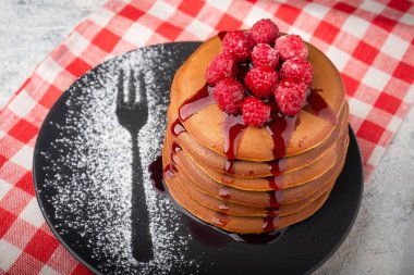 a stack of pancakes on a plate with raspberries and berry sauce, copy space, Close-up