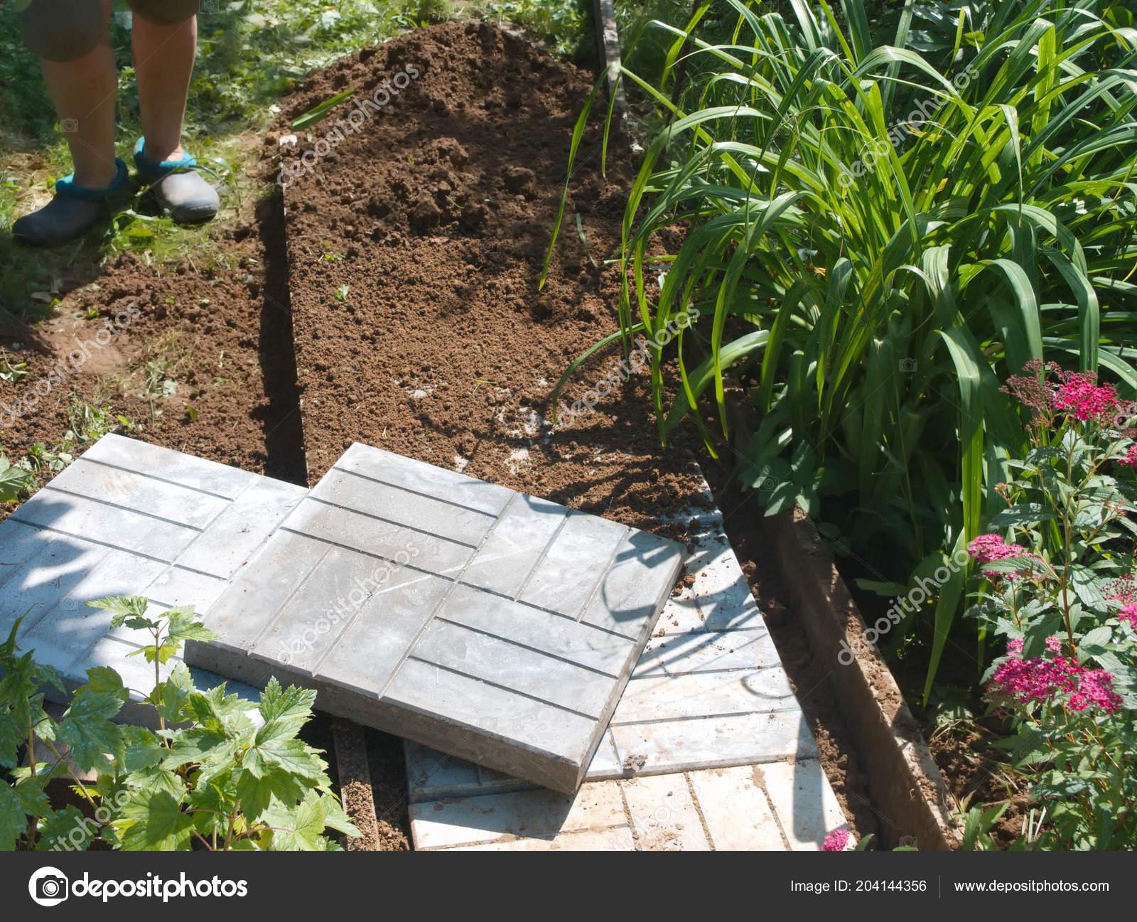 Mattonelle cemento sentiero pavimentazione giardino lavoratore che