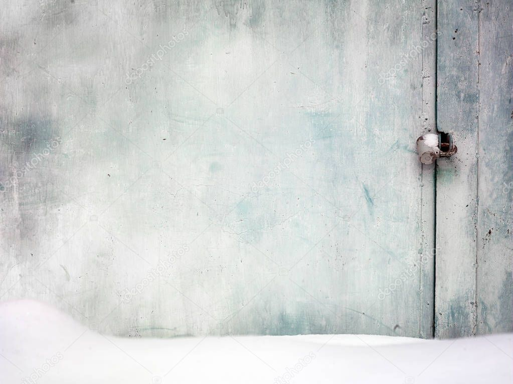 Locked and covered with snow metal door, outdoor cropped shot