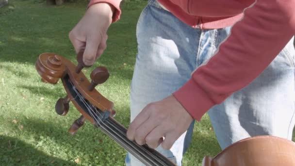 Hudebník, tuning violoncello, stojící v zahradě