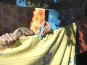 Venkovní closeup ženských rukou připnutí prát prádlo na laně