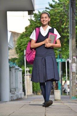 Female University Student Wearing Uniform Walking On Sidewalk