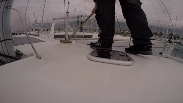Námořník v černém boty čištění palubě plachetnice v marina
