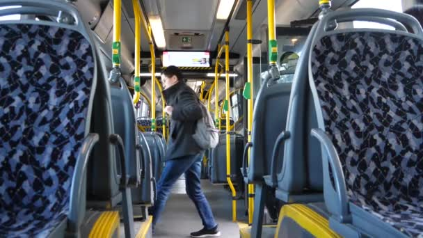 Slow motion footage of man entering bus and seating on place. Inside of public transport in Berlin.