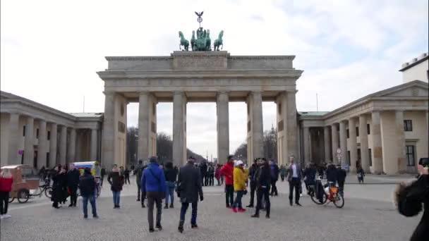 Zeitraffer-Aufnahmen von Menschen, die unter dem Brandenburger Tor in Berlin laufen.