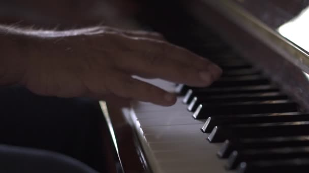 Musician plays piano, in Slow Motion video, in a room with natural light