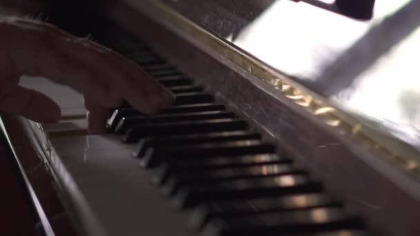 Musiker spielt Klavier, in Zeitlupe, in einem Raum mit natürlichem Licht
