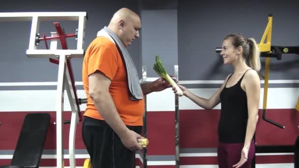 junge schöne Sportlerin versucht, dicke Mann zu motivieren, sich gesund zu ernähren, indem sie ihm Porree gibt, aber Fett weigert sich, es hängenden Hamburger in seiner Hand zu nehmen