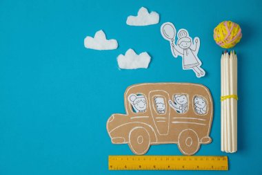 Back to school concept with small children doodles and school bus. View from above