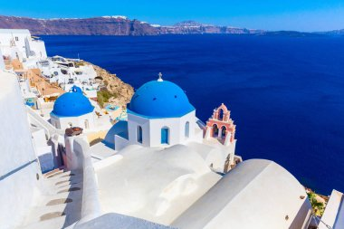 Santorini island, Greece. Oia town traditional white houses and churches with blue domes over the Caldera, Aegean sea.