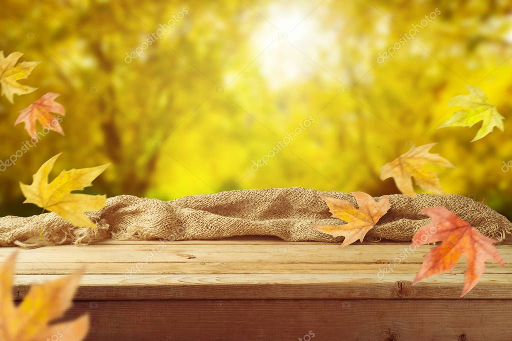 Empty wooden table with sackcloth over autumn leaves bokeh background