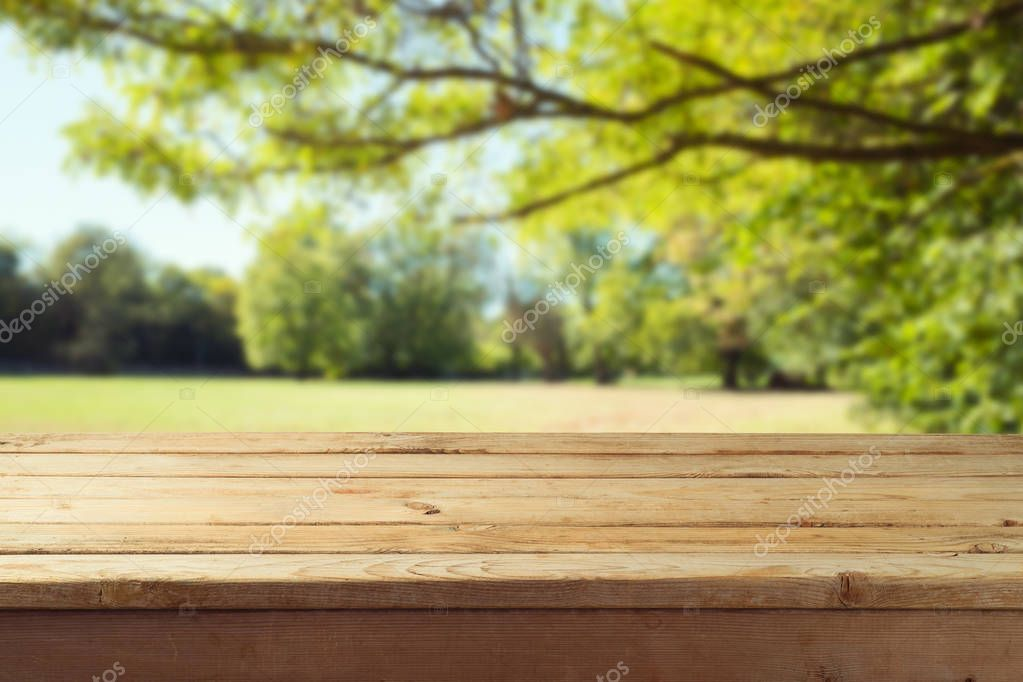Empty wooden table over autumn nature park background